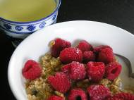 Granola cereal with cranberries, raspberries, almond milk, and green tea