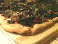 Pizza: red sauce, vegan cheese, chard, kale, green bell pepper, and onion on spelt and whole wheat crust